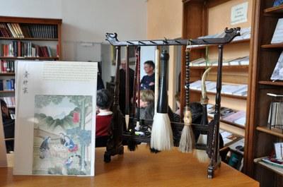 Un fac-similé d'une page de l'album Miao exposé à côté des pinceaux pour la calligraphie.